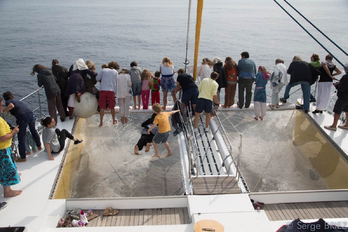 catamaran navivoile croisiere chante avec les dauphins au depart de canet en roussillon avec passagers en observation plage avant du bateau