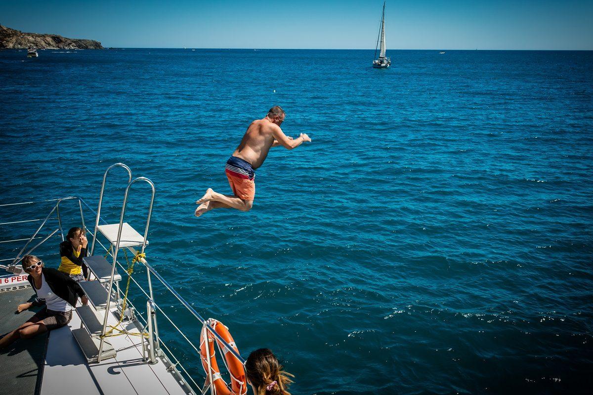 catamaran navivoile croisiere grillade et baignade sur le bateau en baie de paulilles au depart de canet en roussillon ou port vendres plongeon homme